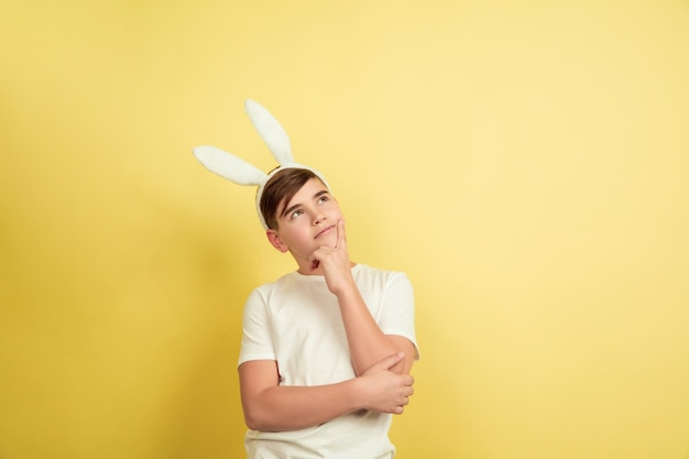 Reflexivo, soñando. chico caucásico como un conejito de pascua sobre fondo amarillo de estudio. felices saludos de pascua. hermoso modelo masculino. concepto de emociones humanas, expresión facial, vacaciones. copyspace.