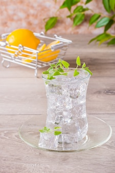 Refrescante agua mineral con cubitos de hielo y hojas de menta en un vaso transparente y limón en una cesta sobre una mesa de madera