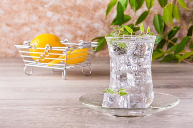 Refrescante agua mineral con cubitos de hielo y hojas de menta en un vaso