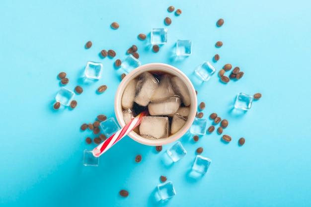 Refrescante café helado en un vaso y cubitos de hielo y granos de café sobre una superficie azul. concepto de verano, cola con hielo, refrescante cóctel, sed. vista plana, vista superior