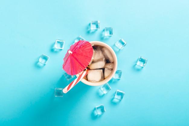 Refrescante café helado en un vaso y cubitos de hielo sobre una superficie azul. concepto de verano, cola con hielo, refrescante cóctel, sed. vista plana, vista superior