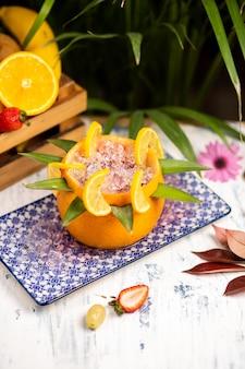 Refrescante cóctel alcohólico de verano, margarita con hielo picado y frutas cítricas dentro de naranja en un auténtico plato decorativo