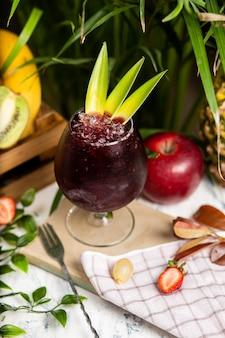 Refrescante cóctel alcohólico de verano, margarita con hielo picado y frutas cítricas dentro de un vaso con fresas y manzana en la mesa de la cocina