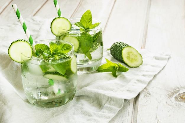 Refrescante cóctel detox de verano. agua con pepino, menta y hielo en vaso sobre una tabla de madera