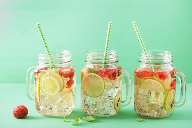 Refrescante limonada de verano con fresa y lima en tarro de albañil