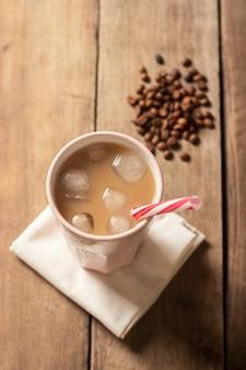 Refrescante y vigorizante café helado en un vaso sobre una superficie de madera. concepto de cafetería, calmar la sed, verano. vista plana, vista superior