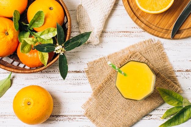 Refrescante zumo de naranja junto a cesta llena de naranjas.