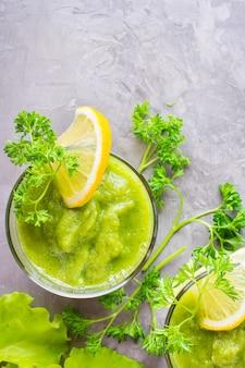Refrescantes batidos de pepino, manzana verde, hierbas frescas y jugo de limón en vasos transparentes sobre la mesa. el concepto de una dieta saludable. menú vegetariano vista superior