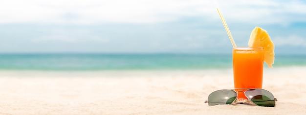 Refrescantes bebidas de jugos de frutas tropicales con gafas de sol sobre fondo de banner de playa de verano