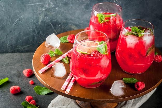 Refrescantes cócteles sin alcohol en verano. bebidas de frutas limonada de mojito de frambuesa con menta orgánica fresca y limón. sobre una mesa de piedra negra. copia espacio