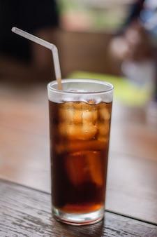 Refresco con hielo en el vaso sobre una mesa.