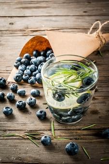 Refrescos de verano bebidas dietéticas. agua de desintoxicación infundida con romero, lima y arándanos. mesa rústica de madera vieja copyspace