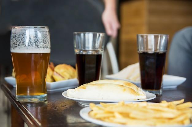 Refrigerio frito con bebidas alcohólicas en la mesa en el bar