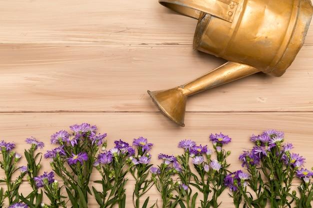 Regadera de cobre y flores de color púrpura.