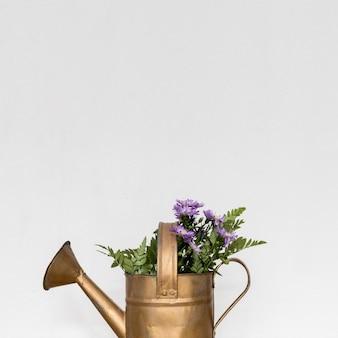 Regadera de cobre con flores.