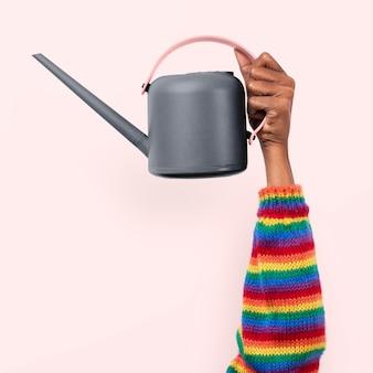 Regadera herramienta de jardinería sostenida por una persona con mangas de arco iris