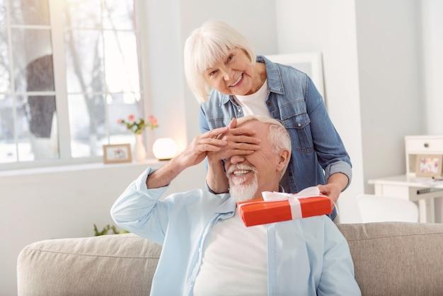 Regalo con amor. pequeña mujer mayor que cubre los ojos de su esposo y le sorprende, felicitándolo con su cumpleaños, habiendo preparado un regalo especial