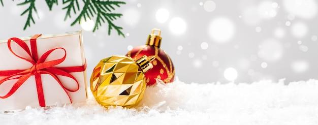 Regalo de año nuevo y bolas de navidad en la nieve sobre un fondo bokeh. tarjeta navideña.