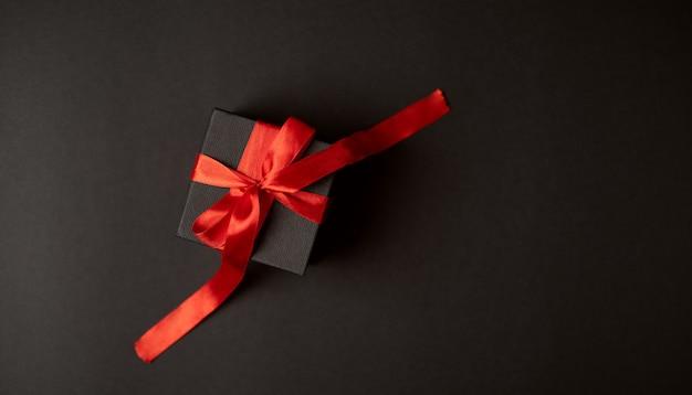Un regalo atado con una cinta roja sobre el fondo oscuro (negro). concepto de san valentín. vista plana endecha, superior.