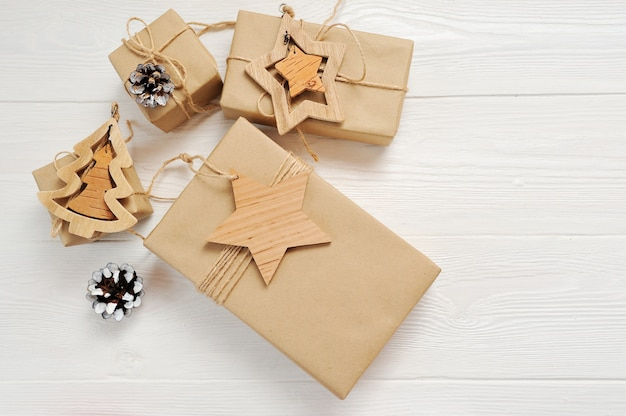Regalo de las cajas de la navidad de la maqueta con la etiqueta y lugar para su texto en un fondo de madera blanco.