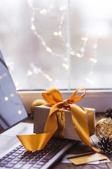 Regalo con una cinta dorada y una computadora portátil y una tarjeta bancaria en una mesa de madera compras en línea de navidad