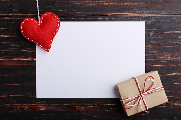 Regalo y corazón de fieltro rojo hecho a mano, junto a papel blanco, sobre mesa de madera