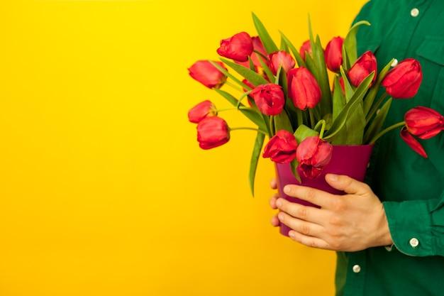 Regalo del día de la madre. un hombre con una camisa verde sostiene un jarrón con un ramo de tulipanes rojos