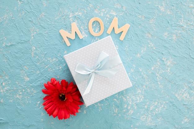 Regalo del día de madres con la flor del rehacer en fondo ligero azul