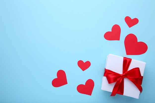 Regalo del día de san valentín con corazones sobre fondo azul.