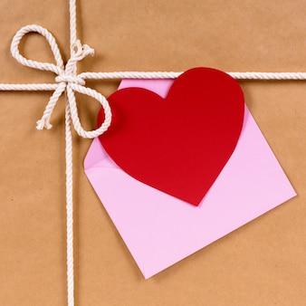 Regalo del día de san valentín con tarjeta en forma de corazón o etiqueta de regalo, paquete de papel marrón