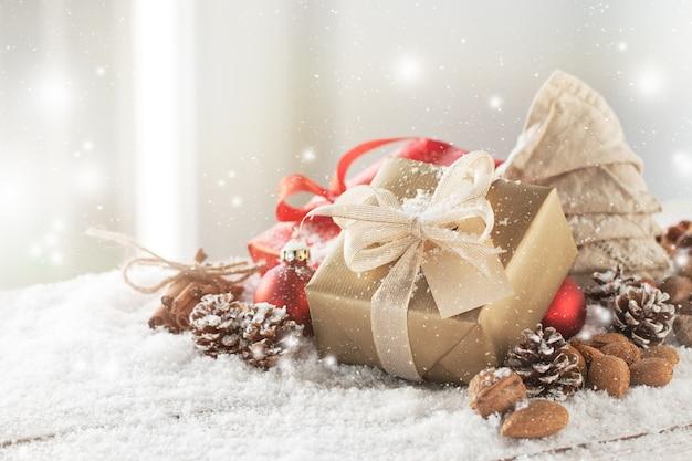 Regalo dorado con lazo blanco sobre adornos navideños