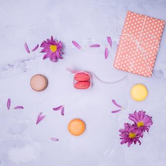 Regalo envuelto con flores moradas y macarons.