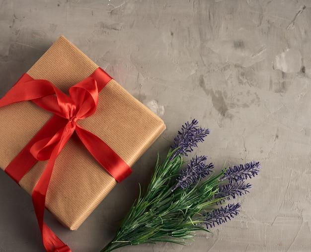Regalo envuelto en papel kraft marrón y atado con un lazo de seda rojo, mesa gris, vista superior, endecha plana