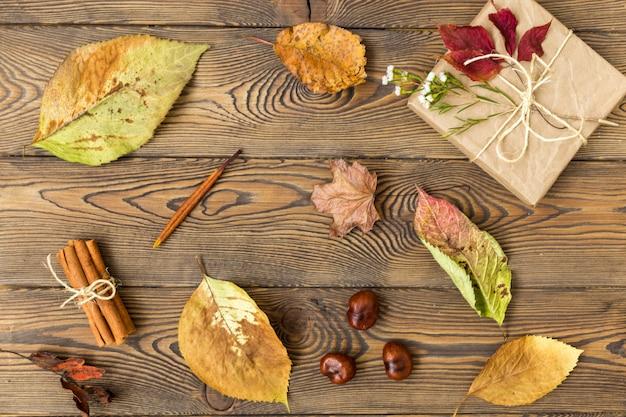 Regalo, hojas de otoño, palitos de canela y castañas sobre fondo de madera.