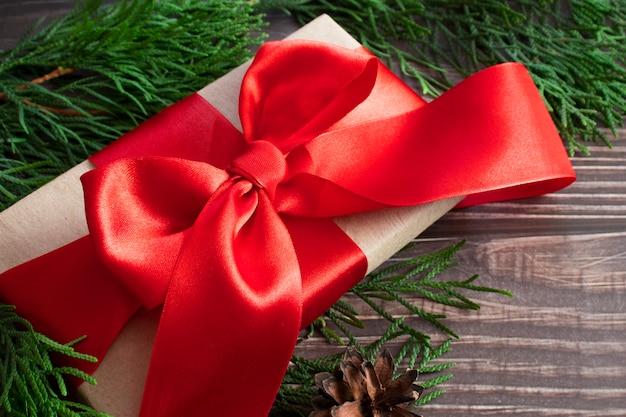 Un regalo con un lazo rojo de cerca sobre un fondo de madera