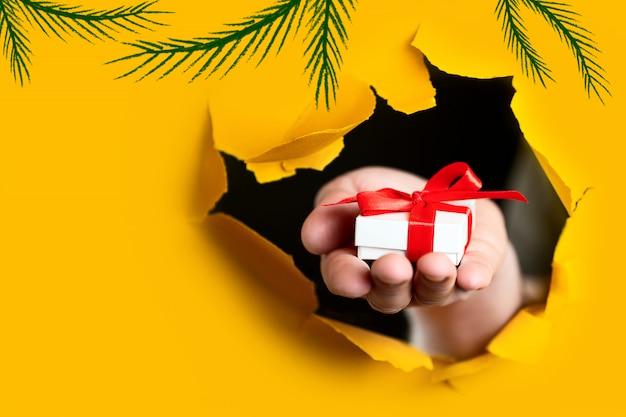 Un regalo con un lazo rojo en la mano emerge de un agujero irregular en el fondo de papel amarillo