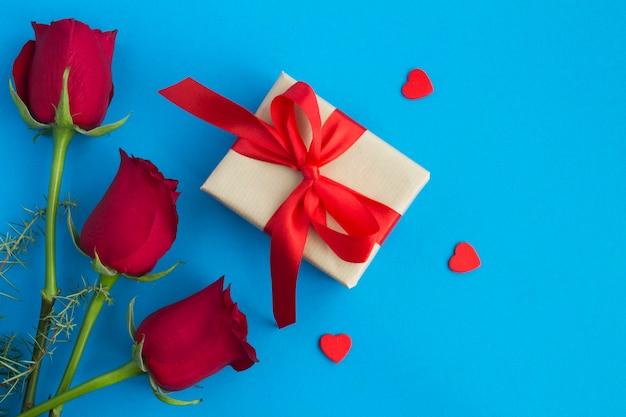 Regalo con lazo rojo, rosas rojas y corazones rojos sobre fondo azul.