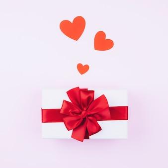 Regalo con un lazo rojo sobre un fondo rosa suave con corazones rojos, para el día de san valentín