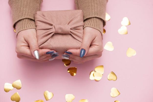 Regalo en manos femeninas con una hermosa manicura.