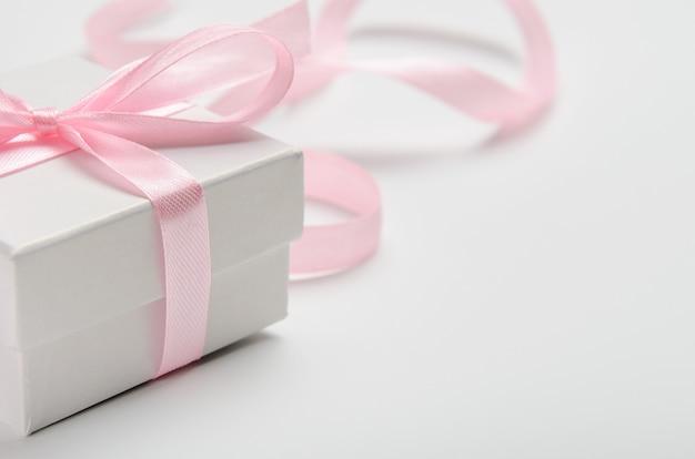 Un regalo para una mujer en caja blanca con una cinta rosa.