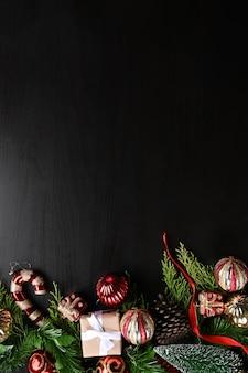 Regalo de navidad, adornos navideños y ramas de abeto sobre fondo negro.