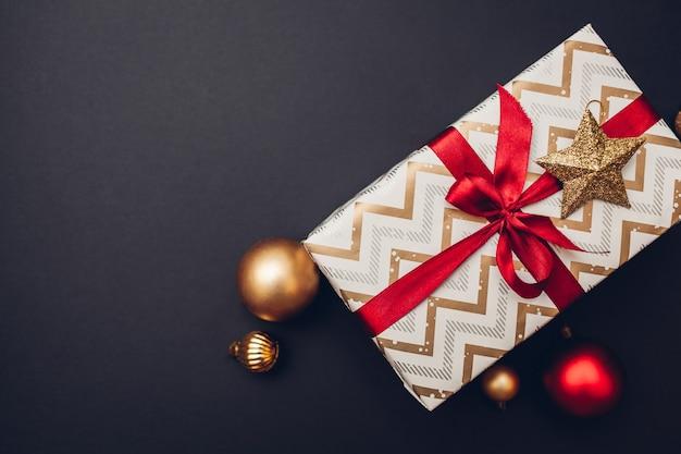 Regalo de navidad y año nuevo envuelto en papel navideño y decorado con cinta roja y juguetes.