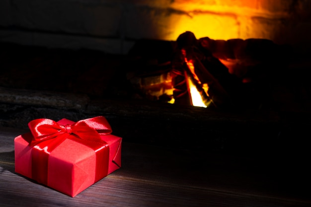 Regalo de navidad cerca de una chimenea encendida sobre una mesa de madera, primer plano