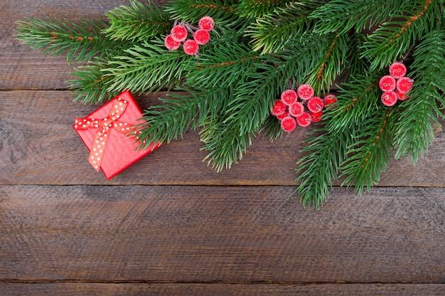 Regalo de navidad, decoraciones y rama de árbol en mesa de madera