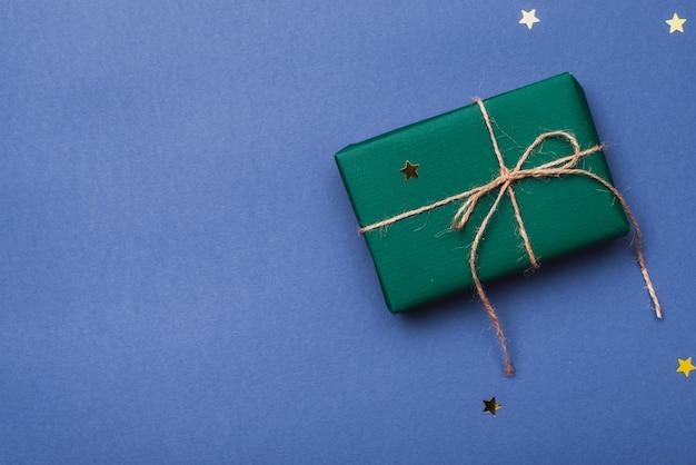 Regalo de navidad envuelto con una cuerda sobre fondo azul.