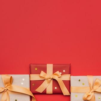 Regalo de navidad envuelto con estrellas sobre fondo rojo.