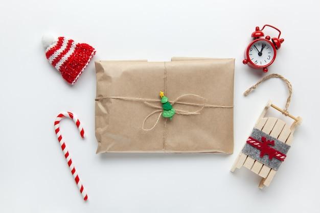 Regalo de navidad envuelto en papel artesanal marrón, atado con flagelo, con bastón de caramelo, pequeño reloj analógico, trineo, gorro en blanco