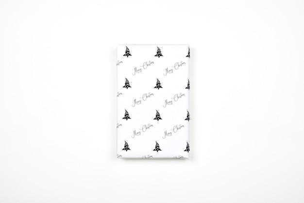 Regalo de navidad envuelto en papel con estampados festivos. regalo de navidad sobre fondo blanco. caja de regalo de navidad brillante casera