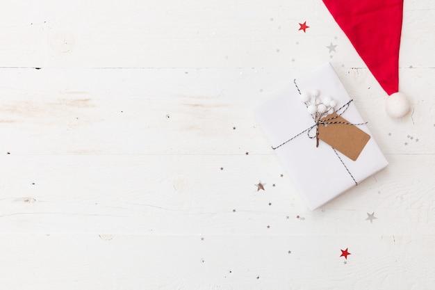 Regalo de navidad envuelto en papel de regalo blanco, adornos navideños y gorro de papá noel en la mesa de madera