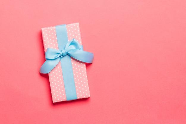 Regalo de navidad hecho a mano envuelto en papel con cinta azul sobre coral vivo